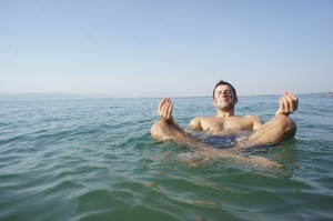 A guy floats cross legged in the Dead Sea